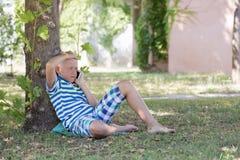 Ein blonder Junge, der auf dem Smartphone spricht Stockfotografie