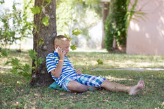 Ein blonder Junge, der auf dem Smartphone spricht Lizenzfreie Stockfotos