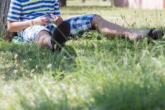Ein blonder Junge, der auf seinem Smartphone spielt Lizenzfreie Stockfotos