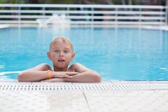 Ein blonder Junge, der lernt zu schwimmen Stockbild