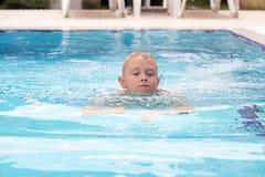 Ein blonder Junge, der lernt zu schwimmen Stockfotografie