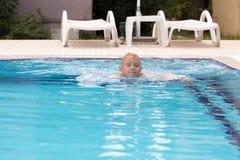 Ein blonder Junge, der lernt zu schwimmen Lizenzfreies Stockfoto
