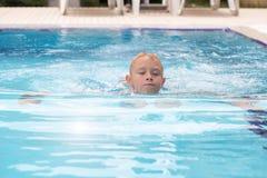 Ein blonder Junge, der lernt zu schwimmen Lizenzfreie Stockbilder