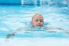 Ein blonder Junge, der lernt zu schwimmen Lizenzfreie Stockfotos