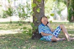 Ein blonder Junge, der an seinem Handy spricht Stockbilder