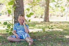 Ein blonder Junge, der an seinem Handy spricht Stockfotografie