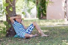 Ein blonder Junge, der an seinem Telefon im Park spricht Stockfotos