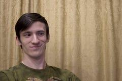Ein blonder Kerl lächelt, sitzt auf einem Stuhl gegen einen Hintergrund von gelben Vorhängen, Blicke weg Lizenzfreie Stockfotos