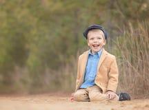Ein blonder Kleinkindjunge, der auf einem Sand und einem Lachen sitzt Stockfotos