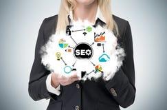 Ein blonder Manager hält eine Wolke mit 'SEO-' Optimierungsflussdiagramm Lizenzfreies Stockbild