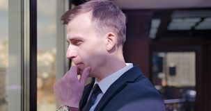 Ein blonder Mann in einem Smoking nähert sich dem Fenster und erwägt, genießt das Panorama, trifft eine Entscheidung Geschäftsman stock video footage