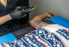 Ein blonder Tattooist, der die Tätowierung fotografiert, die sie sie antut Lizenzfreie Stockfotos