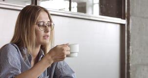 Ein blondes hübsches Modell trinkt etwas Kaffee Stockfoto