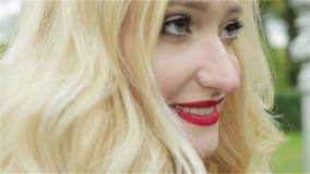 Ein blondes junges Mädchen mit einem roten Lippenstiftlächeln Langsame Bewegung stock video
