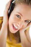 Ein blondes Mädchen, das Musik mit Kopfhörern genießt Lizenzfreie Stockfotos
