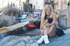 Ein blondes Mädchen mit einer Herzmanschette sitzt auf einem Felsen und hält eine Kamera bei Riomaggiore, La Spezia, Italien stockbild