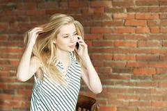 Ein blondes Mädchen nennt durch das Telefon gegen einen Backsteinmauerhintergrund und nennt den Wohnungsreparaturservice bekanntm Lizenzfreie Stockfotos
