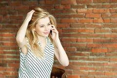Ein blondes Mädchen nennt durch das Telefon gegen einen Backsteinmauerhintergrund und nennt den Wohnungsreparaturservice bekanntm Lizenzfreies Stockfoto