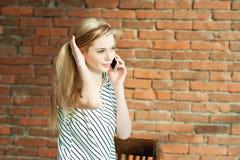 Ein blondes Mädchen nennt durch das Telefon gegen einen Backsteinmauerhintergrund und nennt den Wohnungsreparaturservice bekanntm Stockfotos