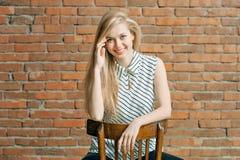 Ein blondes Mädchen nennt durch das Telefon gegen einen Backsteinmauerhintergrund und nennt den Wohnungsreparaturservice Werbung  Stockfoto