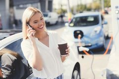 Ein blondes Mädchen trinkt Kaffee und spricht am Telefon an einer Ladestation Stockfotografie
