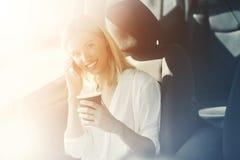 Ein blondes Mädchen trinkt Kaffee und spricht am Telefon an einer Ladestation Lizenzfreie Stockfotos