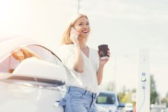 Ein blondes Mädchen trinkt Kaffee und spricht am Telefon an einer Ladestation Stockbilder