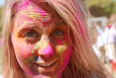 Ein blondes mit Farben auf ihrem Gesicht Frühlingsfest Lizenzfreie Stockbilder