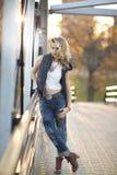 Ein blondes womanl in der städtischen Ausstattung auf Brücke über See-Ufer-Antrieb Stockfotografie
