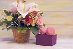 Ein Blumenkorb und ein Kasten Makronen stockfoto