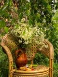 Ein Blumenstrauß der Kamille in einem Lehmvase unter einem Sommerregen stockfotografie