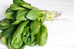 Ein Blumenstrauß des frischen Spinats auf einem Holztisch Lizenzfreies Stockfoto