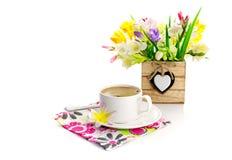 Ein Blumenstrauß mit Blumen und einem Tasse Kaffee