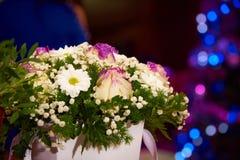 Ein Blumenstrauß von Blumen in einem Kasten auf dem Hintergrund des hellen mehrfarbigen bokeh lizenzfreies stockfoto