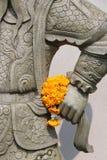 Ein Blumenstrauß von Blumen wurde gelegt in die Hand der Statue eines Kriegers (Thailand) Stockbilder