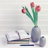 Ein Blumenstrauß von drei roten Tulpen ist in einem grauen Vase Ist in der Nähe ein Stapel von Büchern, von offenen Notizbuch und lizenzfreies stockbild