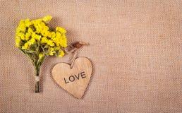 Ein Blumenstrauß von gelben Wildflowers und ein hölzernes Herz auf einem natürlichen Leinenhintergrund Romantisches Konzept Hinte Stockbild