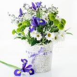 ein Blumenstrauß von Iris blüht in einem Weidenkorb Stockbild