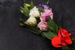 Ein Blumenstrauß von japanischen Rosen verband Bänder mit einem Herzen auf einem Steinhintergrund stockfoto