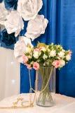 Ein Blumenstrauß von kleinen weißen und rosa Rosen in einem transparenten Schleier Goldperlen Blauhintergrund stockfotos