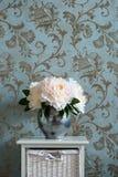 Ein Blumenstrauß von Pfingstrosen in einem Metallvase auf dem Nachttisch im Schlafzimmer stockbild