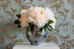 Ein Blumenstrauß von Pfingstrosen in einem Metallvase auf dem Nachttisch im Schlafzimmer lizenzfreie stockfotografie