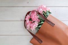 Ein Blumenstrauß von Pfingstrosen in einer Tasche Stockfoto