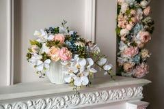 Ein Blumenstrauß von Pfingstrosen, von Orchideen und von Blaubeeren in einem weißen Blumentopf auf einem weißen Kamin in einer kl lizenzfreie stockfotografie