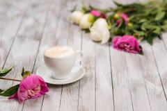 Ein Blumenstrauß von Pfingstrosen und von Tasse Kaffee auf einem hellen hölzernen Hintergrund Lizenzfreies Stockfoto