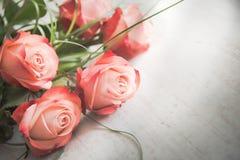 Ein Blumenstrauß von Rosen auf einem weißen hölzernen alten Hintergrund Abbildung der roten Lilie Lizenzfreie Stockbilder