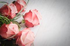 Ein Blumenstrauß von Rosen auf einem weißen hölzernen alten Hintergrund Abbildung der roten Lilie Lizenzfreie Stockfotos