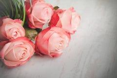 Ein Blumenstrauß von Rosen auf einem weißen hölzernen alten Hintergrund Abbildung der roten Lilie Stockfotos