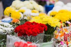 Ein Blumenstrauß von roten Gartennelken und andere Blumen werden im Stadtmarkt verkauft lizenzfreie stockfotos