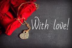 Ein Blumenstrauß von roten Rosen und von Goldmedaillon in Form eines Herzens auf einem hölzernen schwarzen Hintergrund stockfotos